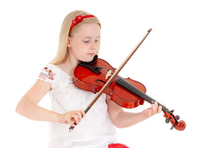Young blonde girl plays violin on a white studio background. Foto de archivo