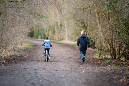A mother walks alongside her young daughter as she rides her bike along a country track.