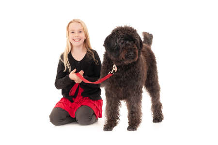 Happy young blonde girl holding black labradoodle on a red leash. Isolated on white studio background
