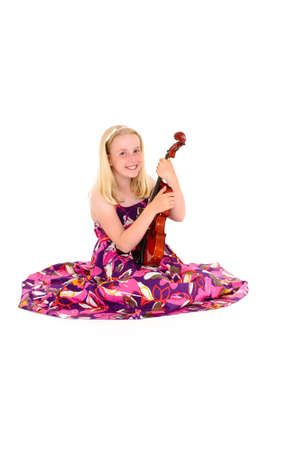 Happy young blonde girl in a wide flowery dress poses with violin on a white studio background. Foto de archivo