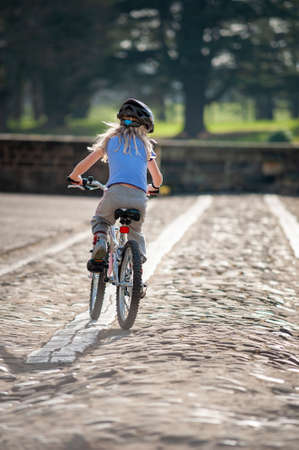 A young blonde girl rides a bike along a cobbled path away from camera in golden sunlight. Foto de archivo