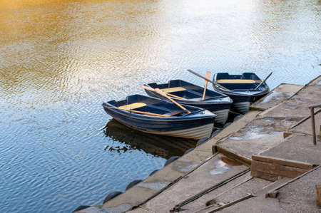 Three blue and white rowing boats moored on a tranquil river on a sunny day. Foto de archivo