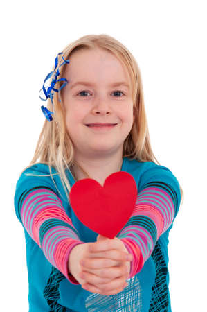 A young blonde girl holding a red heart out in front. Isolated on white studio background Foto de archivo