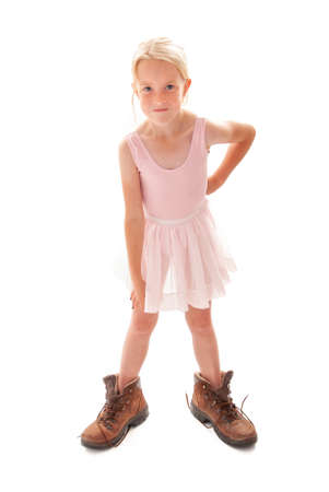 Cheeky young blonde girl dressing up in ballet outfit and Dad's big walking boots. Foto de archivo