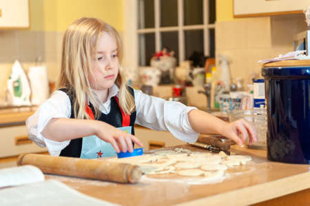 A pretty young blonde girl cutting out dough while baking in a messy kitchen.