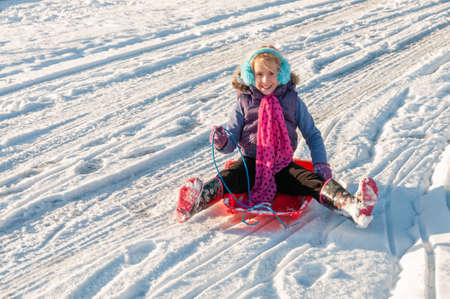 Happy, vibrantly dressed young girl with blue ear muffs sledging down a slope.