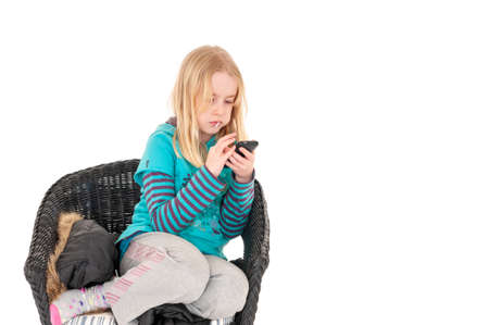 Young blonde girl sat on a wicker chair using a smartphone. Isolated on white studio background Foto de archivo