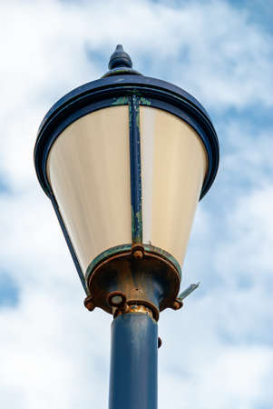Close up of a rusted street lamp with chipped blue paint work.