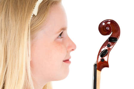 Close up of young blonde girl looking at the head of a violin on a white studio background.