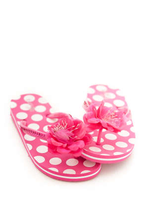 Pink and white polka dot flip flops isolated on a white studio background.