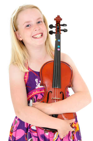 Close up of smiling young blonde girl in a flowery dress posing with violin on a white studio background.