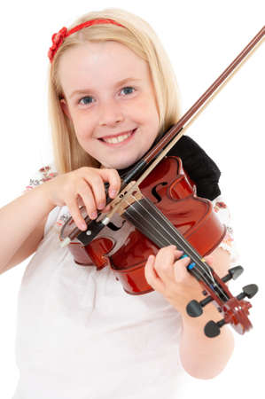 Smiling young blonde girl plays violin on a white studio background. Foto de archivo