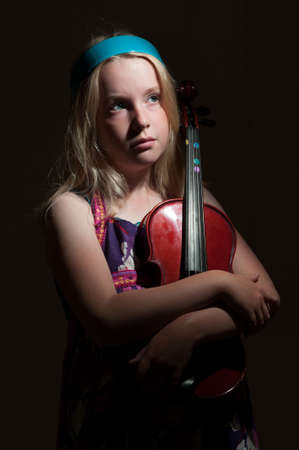 Close up of young blonde girl hugging a violin on a black studio background with moody lighting.