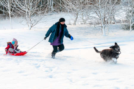 Black dog leading mother with daughter sledging through deep snow in a rural setting.