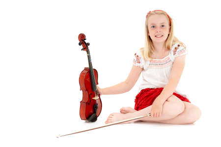 Young blonde girl poses with violin and bow on a white studio background.