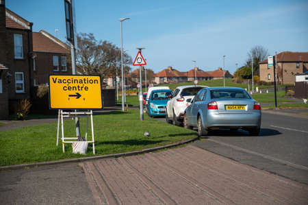 Amble, Northumberland, UK - March 21, 2021: Vaccination Centre temporary road sign on a housing estate with parked cars nearby Editorial