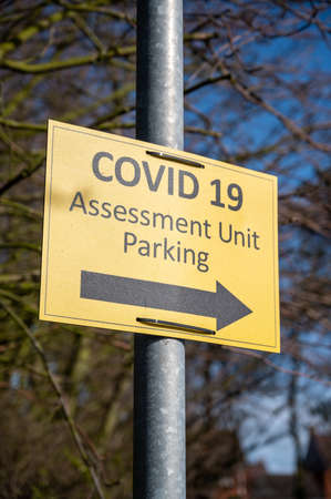 Amble, Northumberland, UK - March 21, 2021: Yellow Covid 19 Assessment Unit Parking sign. Portrait orientation. Editorial