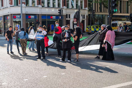 LONDON - MAY 29, 2021: Protesters carrying a large Palestinian flag at a Freedom for Palestine protest rally outside Holborn Tube Station