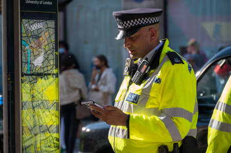 LONDON - MAY 29, 2021: British police officer in a high visibility jacket looks at a mobile cell phone