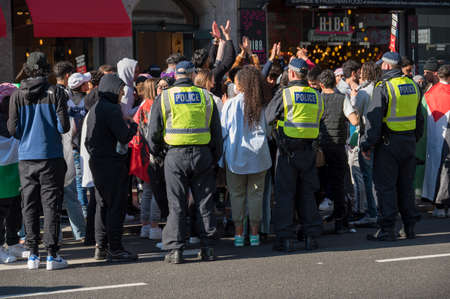 LONDON - MAY 29, 2021: British police officers surround protesters at a Freedom for Palestine protest rally in London Editorial