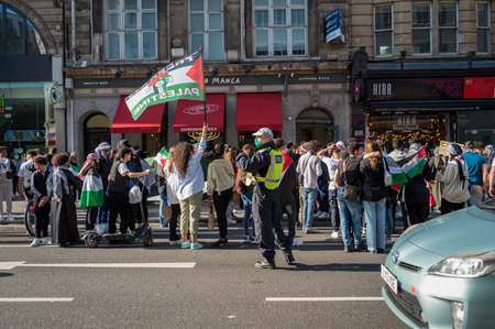 LONDON - MAY 29, 2021: British police officer wearing a PPE face mask at a Freedom for Palestine protest rally in London