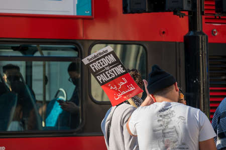 LONDON - MAY 29, 2021: A protester holds a placard sign in front of a red London double decker bus at a Freedom for Palestine protest rally Editorial