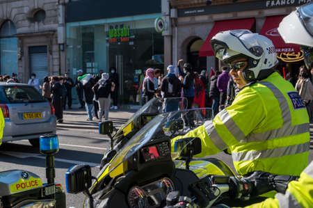 LONDON - MAY 29, 2021: British police motorcyclist with Freedom for Palestine protest rally on a London street in the background
