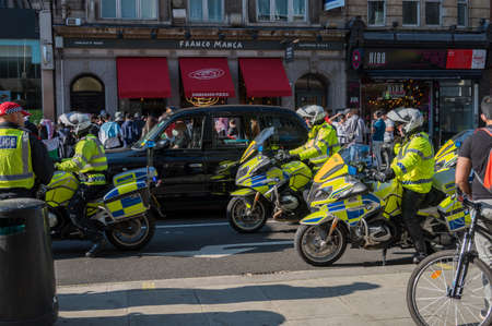 LONDON - MAY 29, 2021: British police motorcyclists and a black London taxi cab at a Freedom for Palestine protest rally Editorial