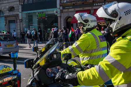 LONDON - MAY 29, 2021: Two British police motorcyclists with Freedom for Palestine protest rally on a London street in the background