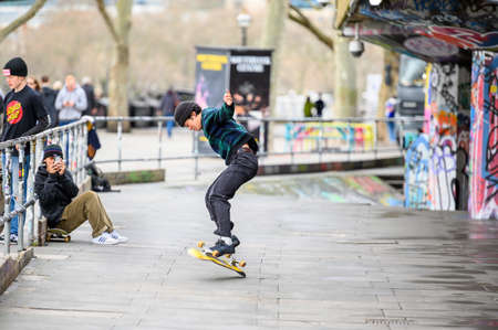 LONDON - MARCH 10, 2020: A group of friends practise skateboarding at a skate park on the South Bank of the river Thames, London