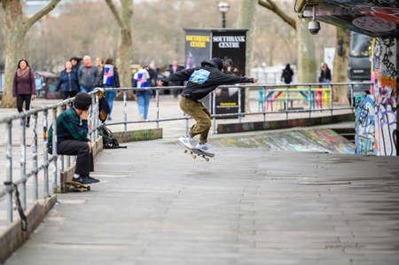 LONDON - MARCH 10, 2020: Young Skateboarder practising his moves with a friend at skate centre on London's South Bank Editorial