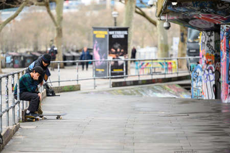 LONDON - MARCH 10, 2020: Friends taking a break from skateboarding at a skate park on the South Bank of the river Thames, London