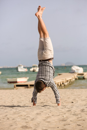 one man: Beach handstand - one man performing on the beach