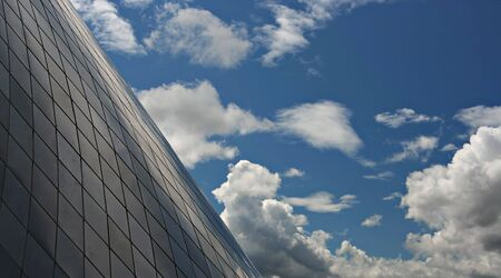 Interesting contrast of a beautiful blue sky full of clouds to the geometric buidling in the foreground