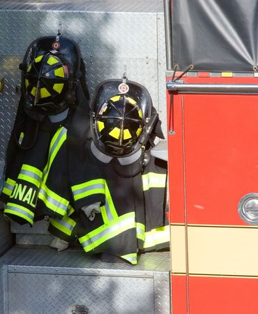 emergency call: Two firefighter�s coats and helmets hang on an engine after an emergency call