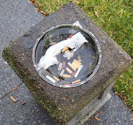 A shot of a waterlogged public ashtray full of garbage