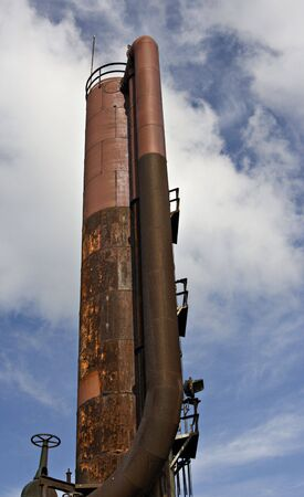 disrepair: A shot of a vertical smoke stack of long forgotten industrial machinery sits in disrepair