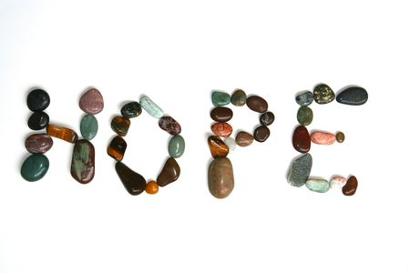 The word Hope spelled out in very colorful polished rocks and gems