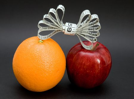 An apple and orange with a tape measure bow isolated on a black background.