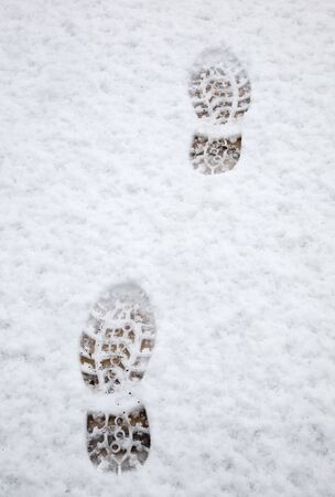 Two footprints in the snow on a wooden deck