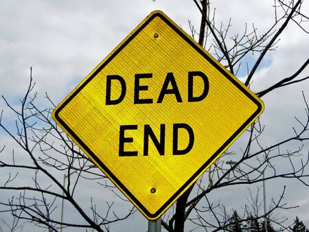 A dead end sign with a defoliated tree in the background lends an ominous tone