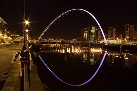 Gateshead Millennium bridge at night / Reflection of the Gateshead Millennium bridge illuminated at night photo