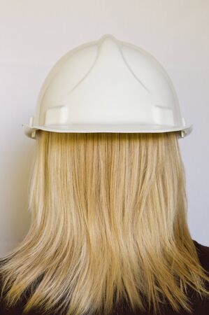 White hard hat reversed on womans head photo