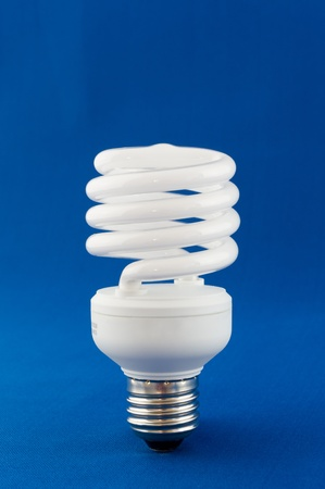 Modern energy saving light bulb on blue background photo