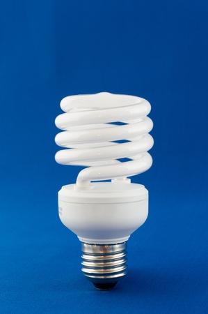risparmio energetico: Moderna lampadina a risparmio energetico su sfondo blu