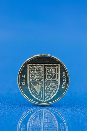 Pound coin with reflection isolated on blue background Stock Photo - 12692674