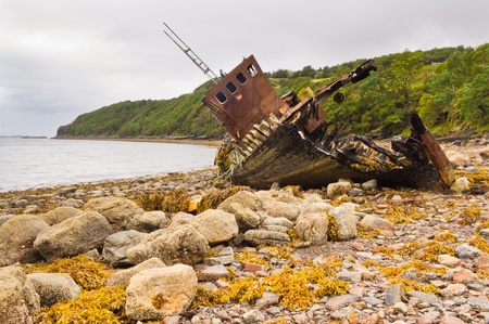 Fishing boat wreck stranded on a pebbled beach photo