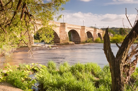 Corbridge in spring showing the bridge over the river Tyne leading into Corbidge village on a sunny day
