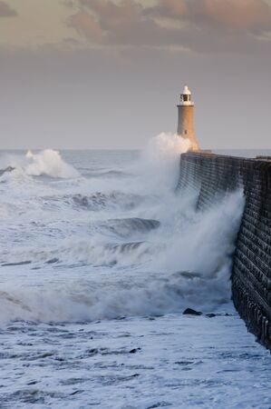 Tynemouth north pier with waves crashing against it and the lighthouse