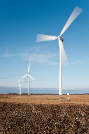Wind turbines showing motion blur on rotating blades vertical